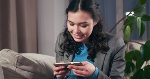 Donna di affari emozionante che gioca gioco sul telefono cellulare archivi video