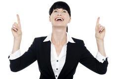 Donna di affari emozionante che osserva annuncio che indica verso l'alto Fotografia Stock
