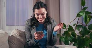 Donna di affari emozionante che per mezzo del telefono cellulare a casa archivi video