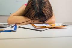 Donna di affari esaurita che dorme sulla sua tavola fotografia stock