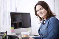 Donna di affari felice al suo scrittorio che esamina macchina fotografica Immagini Stock Libere da Diritti