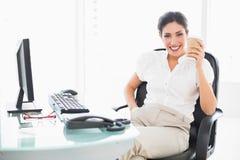 Donna di affari felice che beve un caffè al suo scrittorio Immagine Stock
