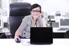 Donna di affari felice che chiacchiera sul telefono all'ufficio Fotografia Stock Libera da Diritti