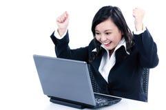 Donna di affari felice che incoraggia davanti al computer portatile Fotografia Stock Libera da Diritti