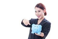Donna di affari felice che indica al porcellino salvadanaio fotografia stock libera da diritti