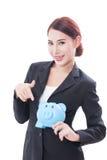 Donna di affari felice che indica al porcellino salvadanaio fotografie stock