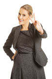 Donna di affari felice che mostra il segno di vittoria Immagini Stock