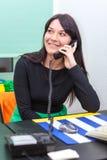Donna di affari felice che parla sul telefono in ufficio Fotografie Stock
