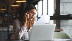 Donna di affari felice che parla sul telefono in un caffè e che scrive su un computer portatile video d archivio