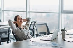 Donna di affari felice che si rilassa con le mani dietro la testa alla scrivania Fantasticare concetto fotografia stock