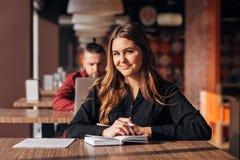 Donna di affari felice che si siede in un caffè con un taccuino e che sorride alla macchina fotografica Immagine Stock