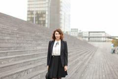 Donna di affari felice che sta sulle scale con la borsa e sulle alte costruzioni nel fondo Fotografia Stock Libera da Diritti