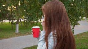 Donna di affari felice con i vetri nelle passeggiate leggere del vestito in caffè bevente del parco e parlare su uno smartphone,  stock footage