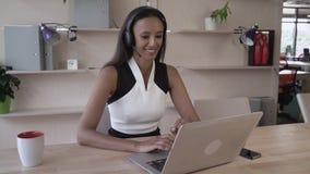 Donna di affari felice della corsa mista che parla sul telefono facendo uso delle cuffie archivi video