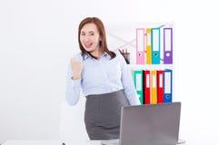 Donna di affari felice e riuscita che alza il suo braccio al fondo dell'ufficio e che celebra successo al fondo dell'ufficio Fotografia Stock Libera da Diritti