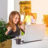 Donna di affari felice emozionante con le armi alzate che si siedono alla tavola con il computer portatile che celebra il suo suc Fotografia Stock
