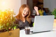 Donna di affari felice emozionante con le armi alzate che si siedono alla tavola con il computer portatile che celebra il suo suc Immagini Stock