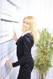 Donna di affari felice vicino alla mensola con i dispositivi di piegatura Immagini Stock