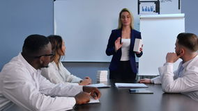 Donna di affari giovane che presenta le nuove compresse o pillole a medici stock footage