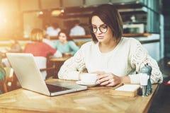 Donna di affari giovane che si siede in caffè alla tavola, al caffè bevente e lavorante al computer portatile Lo studente sta stu Fotografie Stock Libere da Diritti