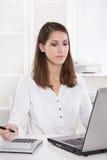 Donna di affari graziosa allo scrittorio con il computer portatile nel bianco Immagini Stock