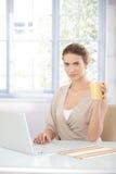Donna di affari graziosa che lavora al computer portatile Immagine Stock