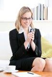 Donna di affari graziosa che trasmette un messaggio di testo Fotografia Stock