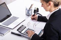 Donna di affari Hand Calculating Invoice che per mezzo del calcolatore fotografia stock libera da diritti