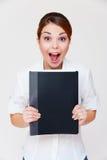 Donna di affari impressionabile con il dispositivo di piegatura nero Immagini Stock