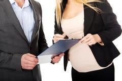 Donna di affari incinta che firma un contratto Fotografia Stock Libera da Diritti