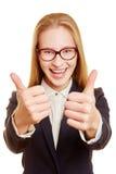 Donna di affari incoraggiante che tiene i suoi pollici su Fotografia Stock Libera da Diritti