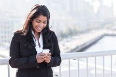 Donna di affari indiana che texting sul telefono Fotografie Stock