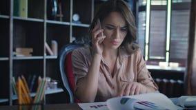 Donna di affari infastidita che risponde sulla chiamata mobile mentre lavorando con i documenti archivi video