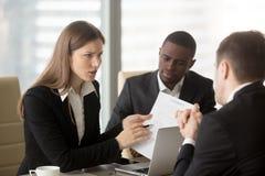 Donna di affari insoddisfatta arrabbiata che discute con l'appaltatore, pointi immagini stock