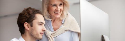 Donna di affari invecchiata del mentore che aiuta al nuovo impiegato con il programma corporativo immagine stock