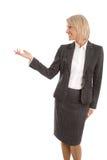 Donna di affari isolata più anziana o matura che presenta sopra il bianco Fotografia Stock