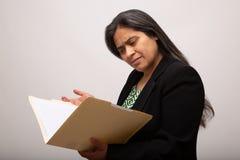 Donna di affari ispana confusa Looks Through Folder fotografie stock libere da diritti