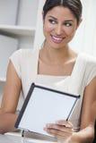 Donna di affari ispana della donna che per mezzo del computer della compressa Immagine Stock