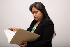 Donna di affari ispana Looks Through Folder fotografie stock