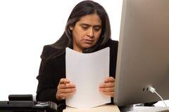 Donna di affari ispana Organizing Paperwork While che parla sul telefono immagini stock