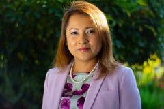 Donna di affari di Latina davanti a fondo verde fotografia stock