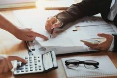 donna di affari di lavoro di squadra che controlla rapporto di finanza stima concentrata immagini stock