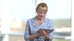 Donna di affari matura bionda con la compressa in ufficio archivi video