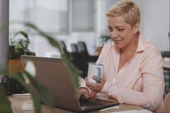 Donna di affari matura che lavora all'ufficio immagine stock libera da diritti