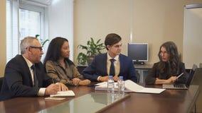 Donna di affari matura che presenta progetto ai colleghi multietnici che utilizzano computer portatile nell'ufficio stock footage