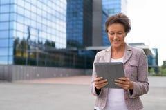 Donna di affari matura felice Using Digital Tablet all'aperto fotografie stock