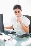 Donna di affari messa a fuoco che beve un bicchiere d'acqua al suo scrittorio Fotografia Stock