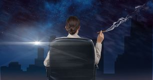 Donna di affari messa in una sedia che fuma e che guarda la città durante la notte Immagine Stock Libera da Diritti