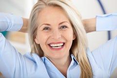 Donna di affari moderna Il bello mezzo ha invecchiato la donna che esamina la macchina fotografica con il sorriso mentre collocav Fotografia Stock