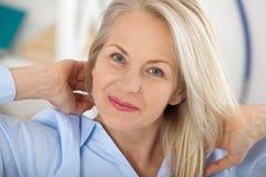 Donna di affari moderna Il bello mezzo ha invecchiato la donna che esamina la macchina fotografica con il sorriso mentre collocav fotografie stock